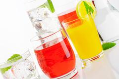 Glasses of fizzy water and fruit-flavored drinks - stock photo