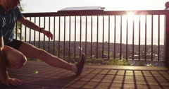 A young jogger stretching in the morning and admiring the view Stock Footage