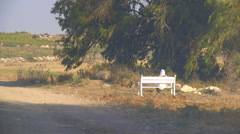Blond woman in a white dress and a white headdress sitting on a bench - stock footage