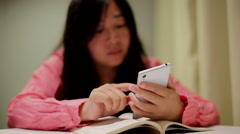 girl playing smartphone while reading book - stock footage
