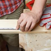 Taking the measurements of the wooden board - stock photo