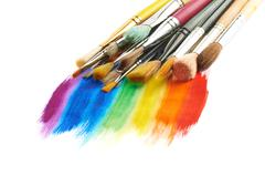 Pile of different brushes over the paint strokes Stock Photos