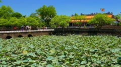 Hue Citadel entrance bridge with visitors and lotus flowers in pond. 4K Stock Footage