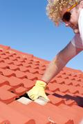 Construction worker tile roofing repairs - stock photo