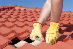 Worker repairing roof tiles on house - stock photo