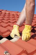 Worker replacing roof tiles on house - stock photo