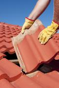 Construction worker tile roofing repair - stock photo