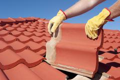 Construction worker tile house roofing repair - stock photo