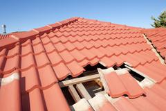 Damaged red tile roof construction house - stock photo