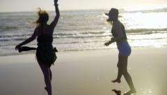 Girls dance toward the water Stock Footage
