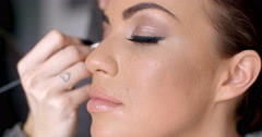 Pretty woman applying eye liner on her eyelid Stock Footage