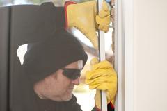 Burglar breaking through window of house Kuvituskuvat