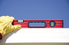Hands with gloves on spirit level outdoor construction Stock Photos