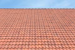 Red tiles roof background and blue sky - stock photo