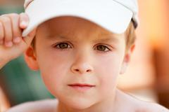Close portrait of a boy with baseball cap - stock photo