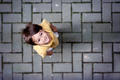 Cute portrait of little boy, standing on the street, looking up - stock photo