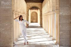 Confident happy mature woman historic archway - stock photo