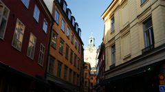 Tilt down to a Street in Gamla Stan with the Royal Palace Church Stock Footage