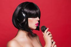 Stylish girl singing with a mike, red background Stock Photos