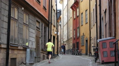 Man running in a street in Gamla Stan Old town Stockholm Sweden Stock Footage