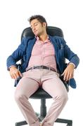 Stock Photo of Overworked, tired young businessman sleeping on office chair