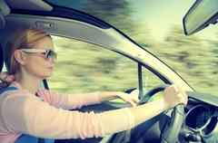 Pretty woman in sunglasses driving fast car filtered and toned - stock photo
