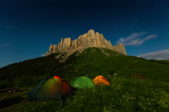 Tourist tent glowing in the night on a background of mountains Big Thach. - stock footage