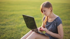 Young Girl Working On A Laptop While Sitting On A Green Lawn - stock footage