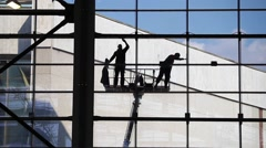 Two unrecognized washers washing windows.Industrial Climbers, facade cleaning Stock Footage