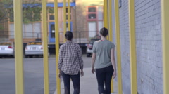 Dancers Walk Down Sidewalk (Away From Camera) In Urban Area, Slow Motion Stock Footage