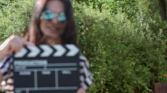 Stock Video Footage of Happy girl with clapboard windy summer day on a background of green leaves