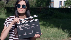 Beautiful girl with clapboard goes to the camera Stock Footage