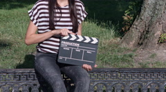 Thin-haired girl with clapboard in the park Stock Footage