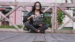 The girl - hippies sitting in lotus position with clapboard glasses Stock Footage