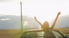 Happy Couple driving convertible car cabriolet on a background sunset Stock Footage