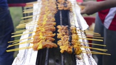 Street hawker grilling satay meat over a gas stove. Stock Footage