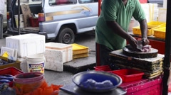 Fishmonger cutting and whacking a fish at a wet market Stock Footage