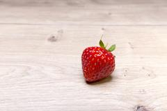 single fresh strawberry on a wood table - stock photo