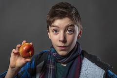 Portrait of a male teenager eating an apple with winter jacket, isolated on g Stock Photos