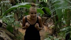 A young woman walking through a tropical jungle. Stock Footage