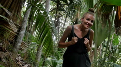 A young cheerful woman waking through a tropical jungle. Stock Footage
