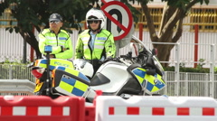 Police officers directing traffic on Hong Kong street Stock Footage