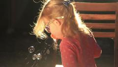 SMALL GIRL BLOWING BUBBLES Stock Footage