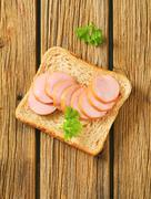 Whole wheat bread with slices of lean sausage - stock photo