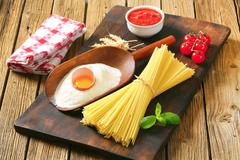 Dried spaghetti, tomato puree and other ingredients - stock photo