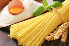 Bundle of dried spaghetti, scoop of flour and fresh egg - stock photo