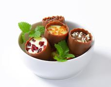 Delicate milk chocolate cups with liqueur and ganache centres Stock Photos