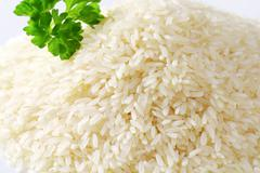 Heap of uncooked white rice - stock photo