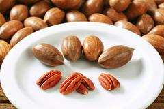 Fresh shelled and unshelled pecan nuts - stock photo