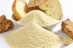 Pieces of stale bread and pile of finely ground bread crumbs Stock Photos